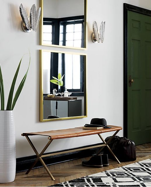 Antique brass and rich leather take on a minimalist, modern shape in CB2's Director's bench, which can be used as an entry perch, a cocktail table, or dining table seating.