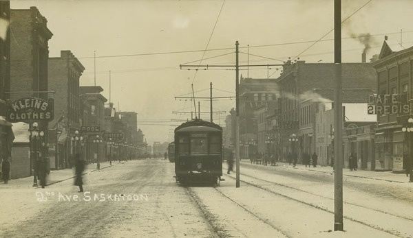 A winter scene of 2nd Avenue, Saskatoon. Kleins Clothing Store can be seen on the left. Trolley cars are travelling up the middle of the Avenue. Gift of the Frances Morrison Library (Main) Local History Room