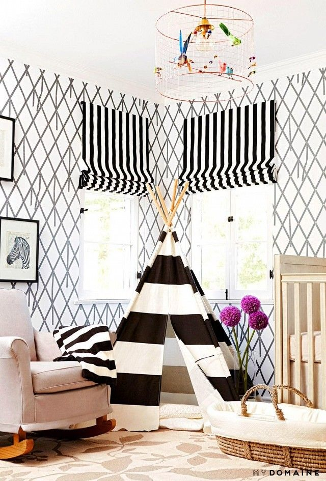 A nursery with muted printed wallpaper, striped blinds, and a play tee pee