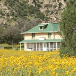 A ranch house with flowers and mountains in the background