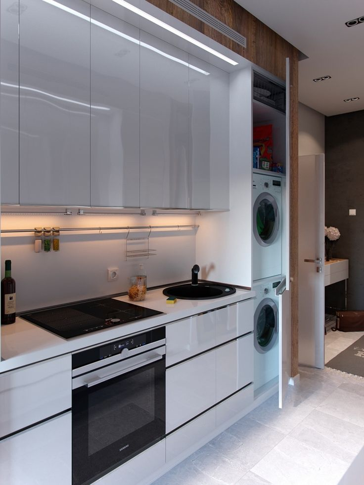 Galley kitchens without windows often run the risk of looking too dark. Here, glossy surfaces preserve what little sunlight the space does receive. Even the door joins in!