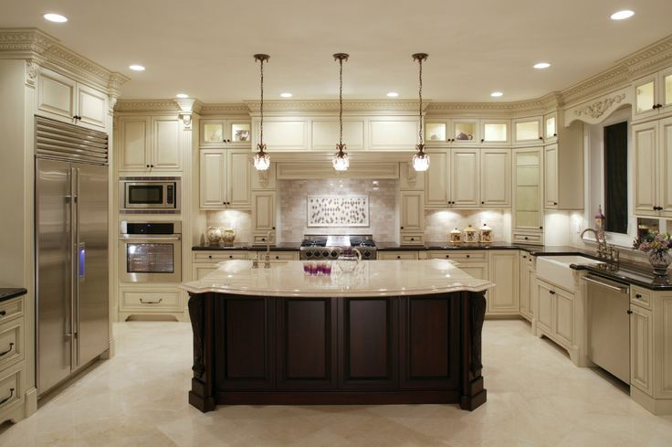 This U-shaped kitchen centers around a large dark wood island with classic marble countertop. Surrounding counters in black, with white cabinetry, add contrast.