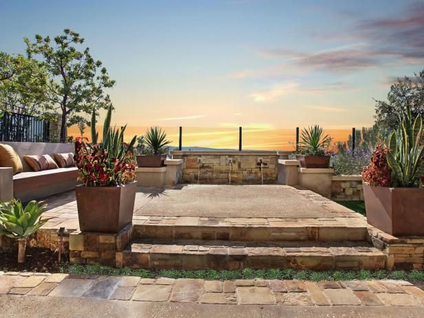 An  elevated courtyard  in a southwestern themed landscape provides a spectacular setting for outdoor entertaining, accompanied by the soothing sounds of flowing water from the bordering wall fountain.