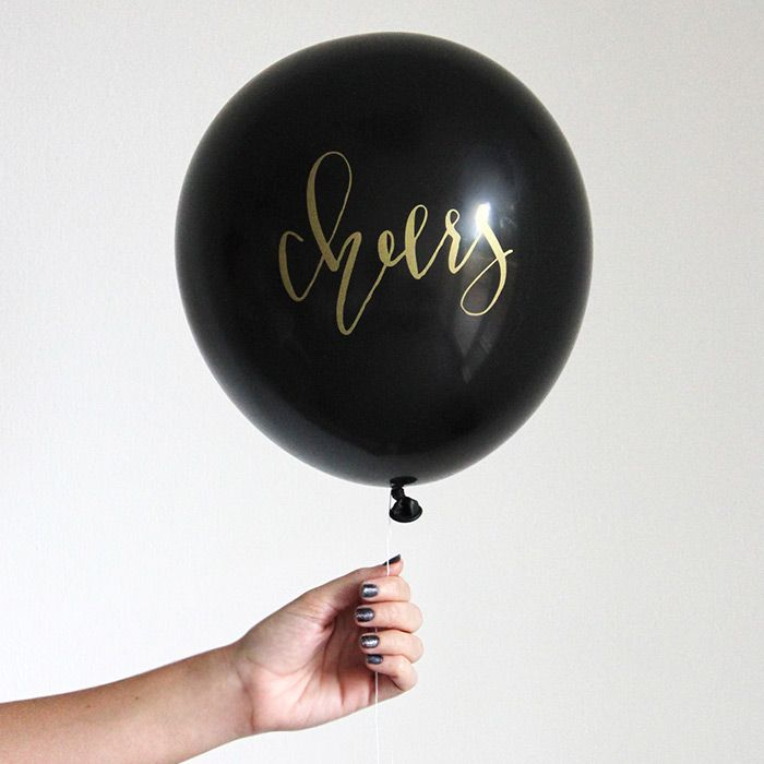 Black and gold Cheers calligraphy balloons, perfect for any celebratory gathering.