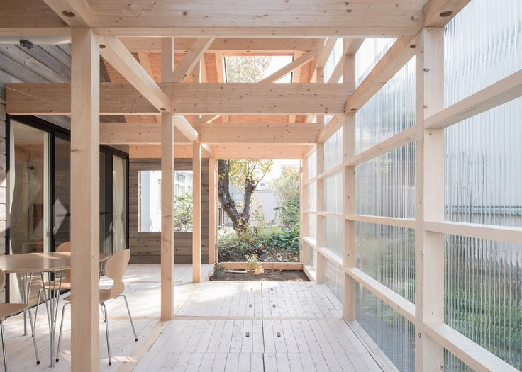 Corrugated plastic surrounds a sunroom at one end of this timber framed residence by japanese