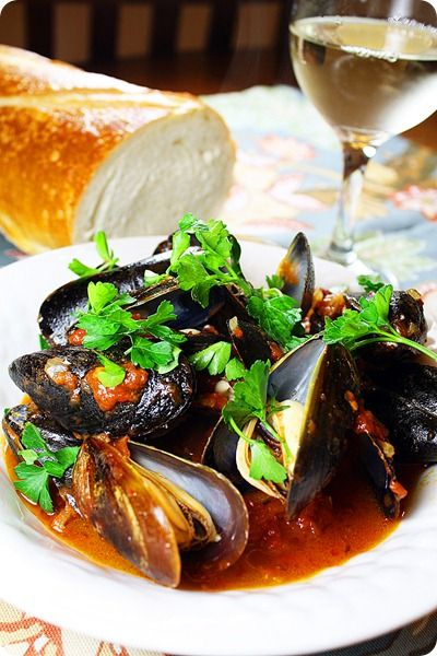 STEAMED MUSSELS IN WHITE WINE & TOMATO SAUCE  Ingredients  2 garlic cloves, minced  1/4 teaspoon dried hot red pepper flakes  1 ½ tablespoons extra-virgin olive oil  1/2 cup dry white wine  2 cups tomato sauce (recipe below)  2 pounds mussels, scrubbed