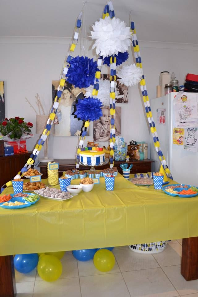 Bananas in Pyjamas themed party set up featuring tissue paper pom poms and partyware from The Reject Shop. Blue, Yellow and White theme, hand made paper chains and labels.