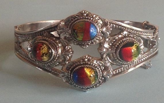 Whiting and Davis ( signed) dichroic glass demi parure set. Included is a clamper bracelet in highly detailed silver tone, and set with 4 dichroic glass ovals. Would suit a smaller to medium sized wrist. Approx 6 cm across when closed. The brooch is also set with 4 dichroic glass stones, as is the beautiful pendant. Both pendant and brooch are approx 2 inches across. A beautiful eye catching piece in excellent vintage condition. A rare and stunning example of Whiting & Davis' work.
