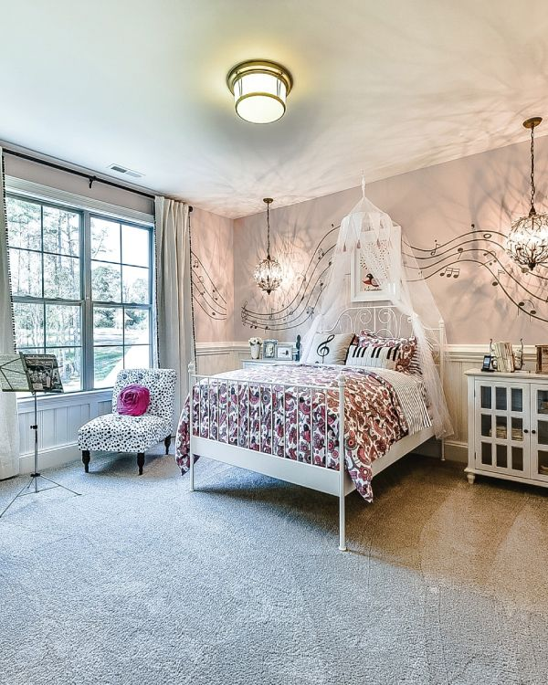 Music themed pink girls bedroom with music notes across the wall and faux canopy bed. The chandelier and white bedroom furniture give this room a whimsical feel. From our Grayson model