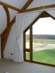 White curtains hung from a lathe which covers the track. The tieback pulls the curtain well clear of the beautiful apex window to maximise the light and the view.