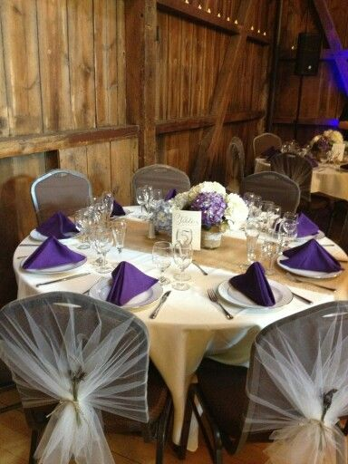 """DIY chair covers with tool, twine, and dried lavender springs for a more modern take on the """"traditional satin cover"""". Centerpieces of hydrangeas in mason jars at different heights. Burlap runner, purple napkins. Table numbers placed in DIY wine cork holders, tied with twine."""
