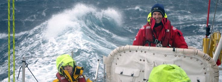 Crew member shown smiling on the helm with large waves behind him