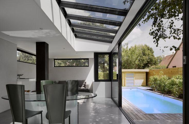 Véranda avec verrière design donnant sur une terrasse avec piscine