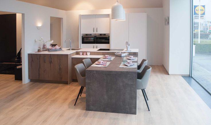Moderne keuken met kookeiland in L-vorm. Deze keuken heeft zowel kolomkasten en ingebouwde toestellen aan de muur, als een kookeiland in een L-vorm. De keukenkasten aan de muur zijn voorzien van grote schuifdeuren waardoor de inbouwtoestellen mooi kunnen opgeborgen worden. Hierdoor krijgt de keuken een nog moderner effect. Anderzijds zorgen de ruwe deuren in het eiland voor een natuurlijke en warme aanvulling. Aan het kookeiland is een tafel aangemaakt zodat in keuken kan worden gegeten