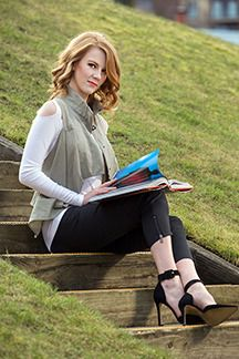 Simone takes a reading break on the steps of the False Creek Community Centre, wearing a Sarah Pacini vest, cut-out sweater and capri pants,...