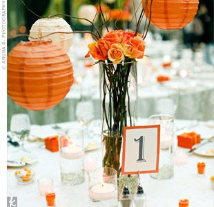 Arrangements of orange and yellow circus and spray roses decorated the reception tables and matched the bridal bouquet. Orange and ivory lanterns with LED lights hung from curly willow branches and added a warm glow to the centerpieces.
