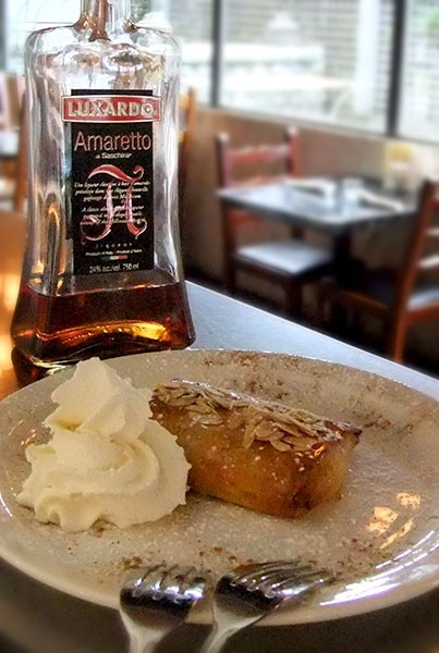 flaky phyllo pastry with a soft Amaretto infused custard center, baked and served warm. Finished with a dusting oficing sugar and sliced almonds then topped with a honey syrup. A Greek Favorite!