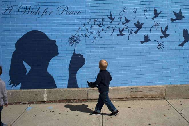 "A Wish for Peace ...Cool Moment Captured..Reuters most liked Instagram images of 2014 - ..© Brian Snyder A boy looks up at a mural reading ""A Wish for Peace"" in Medford, Massachusetts, on September 15."