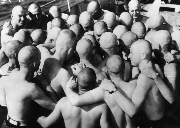 20th August 1943: This group of US Coast Guardsmen huddle together vowing to remain bald until they sight and sink an enemy submarine. (Photo by Keystone/Getty Images)