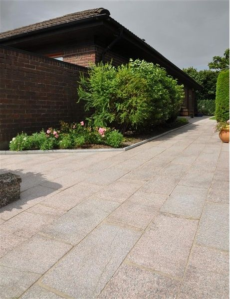 Huggen granit med flammad yta i en lugn röd/rosa nyans. Ger en vacker och naturlig yta för den som vill skapa sig en exklusiv utomhusmiljö. En äkta granit slår alltid en gjuten marksten i betong både i kvalitet och look.