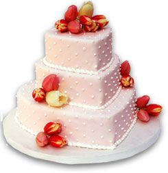 A three-tier heart-shaped cake wrapped in pale pink fondant dotted with pearl-like beads and fresh sprouting tulips by Wonder Bakery
