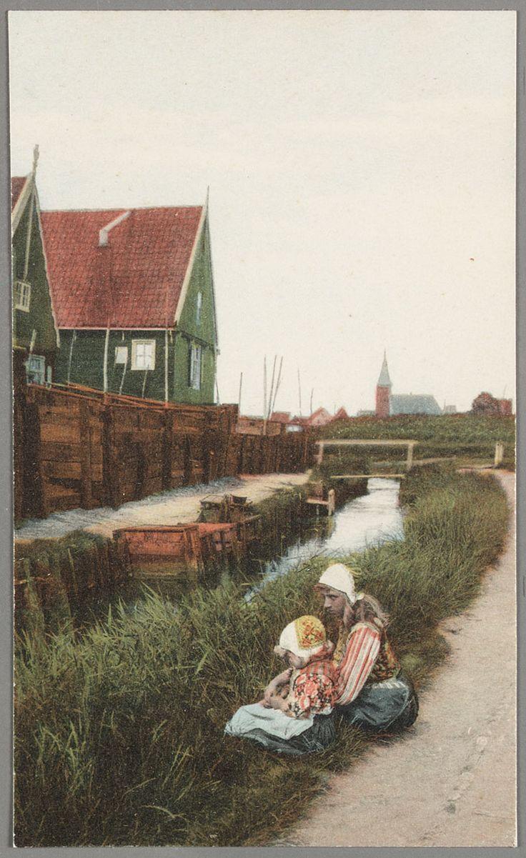 Kinderen in Marker dracht in de wal naast een sloot met aan de overkant houten huizen achter een schutting. In de verte de Ned. Herv. Kerk op de Kerkbuurt. 1910-1920 #NoordHolland #Marken