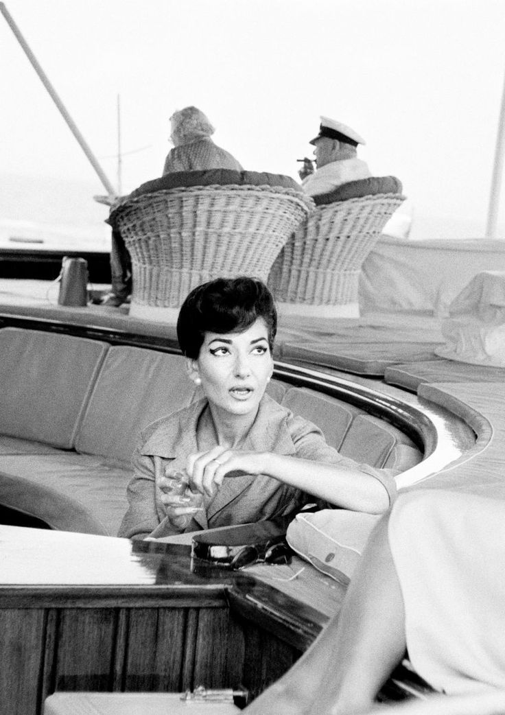 "Maria Callas onboard the Onassis yacht 'Christina O."" with Winston Churchill in the background"