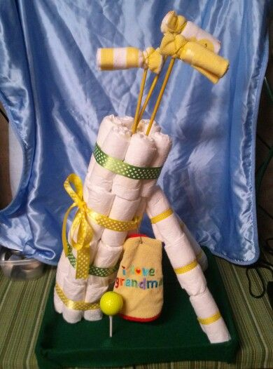 Diaper golf bag. I made this for a grandma shower. It was super easy. Roll 7 diapers for each of the four tiers. I used paper towel roll to hold the golf clubs which are Dowels and wash clothes. I used a baby safety pin to put on the grandma bib. It was a little wobbly so i covered a shoe box lid with green felt and added a tee and golf ball for fun.