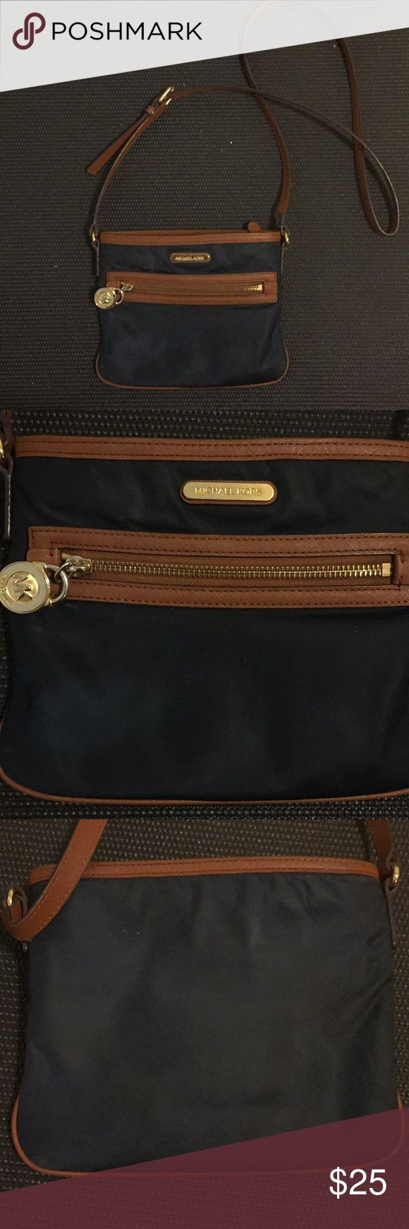 Michael Kors navy blue crossbody Pre loved Michael Kors nylon and leather crossbody bag.  Is a super nice navy blue nylon and light brown leather. Gold zipper and accents with Michael Kors lock zipper pull on front. Has normal wear and tear. Interior of bag doesn't have stains. Small scuffing on corners of the bag. The strap is in good condition. Just has the start of a little bit of cracking in the leather. Otherwise just has normal wear and tear. Michael Kors Bags Crossbody Bags