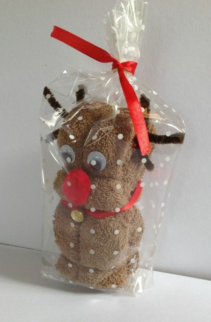brown fluffy towel made to look like a reindeer, with red collar and a golden bell, googly eyes, brown wire antlers and red pom pom nose stuck on it, in clear plastic wrapping paper tied with red ribbon