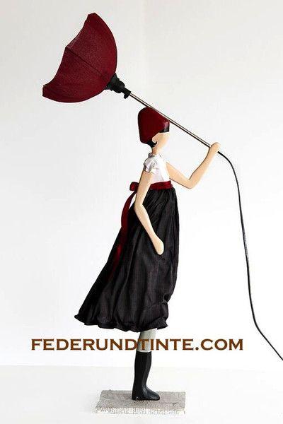 das ist mal eine etwas andere tischlampe eine dame die in einer hand einen regenschirm h lt im. Black Bedroom Furniture Sets. Home Design Ideas