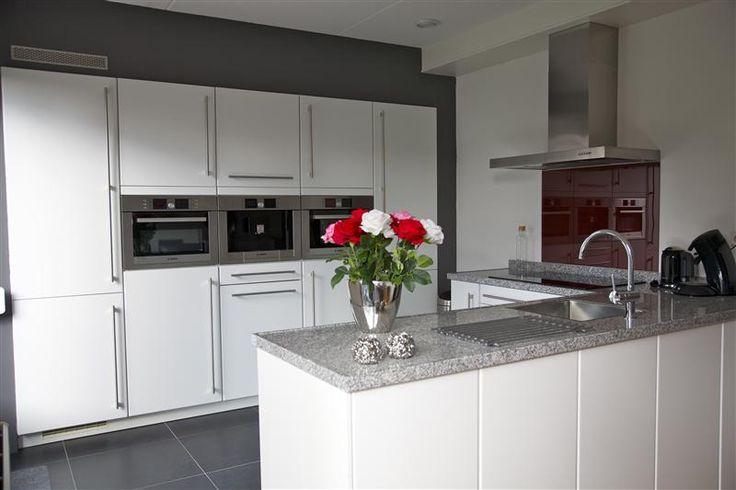 Moderne open keuken. De apparatuurwand is praktisch ingericht en ...