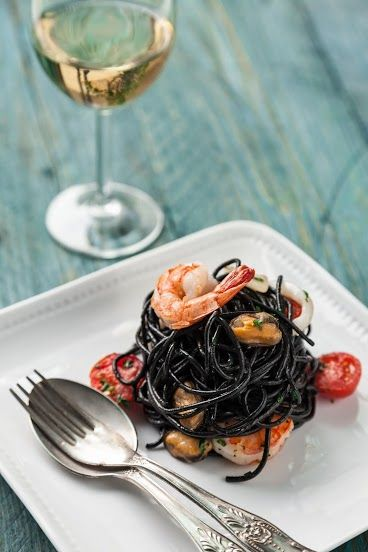 CZARNY MAKARON AGLIO OLIO Z OWOCAMI MORZA krewetkami, łososiem, mięsem muli i kalmarami /  Black aglio olio pasta with Tiger prawns, salmon, mussels meat and squid.