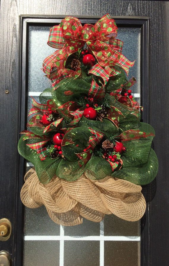 This glittering Christmas tree wreath has been carefully sculpted out of deco mesh, adorned with pomegranate, pear, or apple picks with pine cones and complementary ribbons. Tree can sit on floor resting against a wall or fireplace screen, so it can be used as a smaller substitute for a full-sized Christmas tree, a feature great for dorms or apartments. Measures approximately 26 - 28 tall and 21 - 22 wide.  Add battery operated lights that automatically come on at dusk for 6 hours to any…