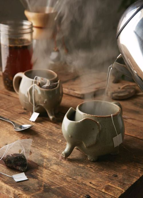 A handmade stoneware tea mug shaped like a cute little elephant with a handy compartment to stash a tea bag after brewing.