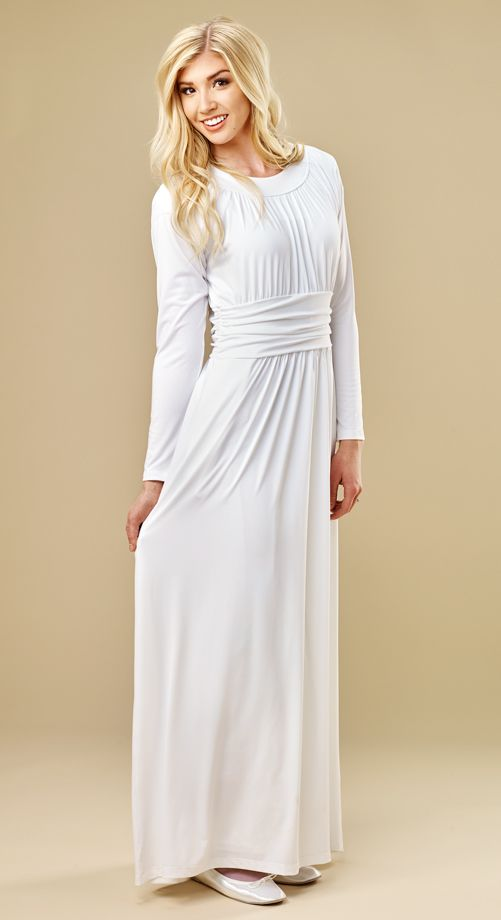 This easy-care knit dress is soft and comfortable, has a ruched band at the waist, contemporary neckline, fuller sleeve, and easy over the head fit.