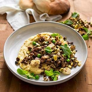 Serve this garlic- and cumin-flavored ground lamb recipe as a topping for hummus, or double the serving size, add some pita and a side salad and you've got an easy and healthy weeknight dinner.