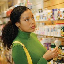Office of Dietary Supplements National Institute of Health | Woman looking at shelves of dietary supplement bottles
