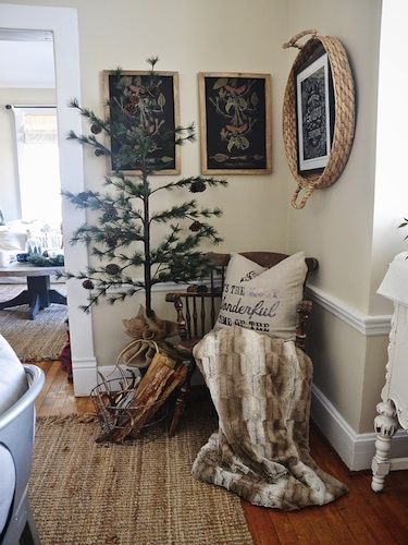 An airy tree from Balsam Hill, festooned with pinecones, picks up the browns in the cozy throw blanket, wooden Windsor chair, and woven basket, which doubles as wall art for a picture frame.