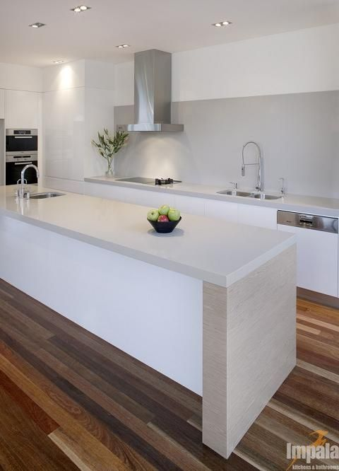 white gloss kitchen with grey worktops and splashback and wood floors