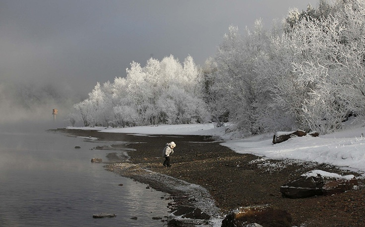 Siberia, Russia: a child walks on the bank of the Yenisei river, with the air temperature at about -23C.    Photograph: Ilya Naymushin/Reuters