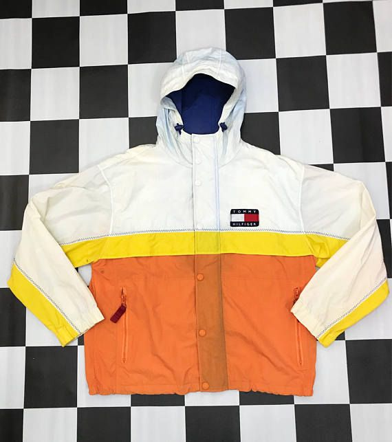 This is the Vintage 90s Tommy Hilfiger Small Flag Hoodie Windbreaker Jacket. A great Tommy Hilfiger jacket with nice colorway (off white, yellow & orange). The unique feature of this jacket is you can fold it and it become Tommy Hilfiger Bag. The jacket is in great condition as like