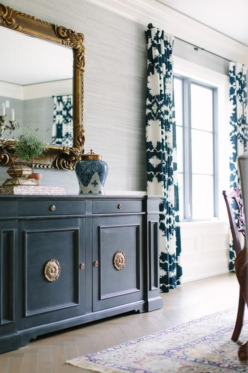 Chic gray and blue dining room features walls clad in platinum gray grasscloth lined with a deep blue buffet cabinet adorned with brass knobs and a gold ornate mirror next to windows dressed in blue curtains in Mary McDonald Garden of Persia Fabric.