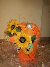 """cesto, dimensioni 30 h e 25 diametro circa, è completamente rivestito di stoffa pannolenci arancio, abbracciato da un giro di raffia che si chiude davanti in un grande fiocco sul quale sono stati applicati grandi girasoli in stoffa, ai quali fa da contorno un pupazzino """"fiore"""" in carta dei colori del cesto …. una vera chicca che non ha eguali …. nè troverete mai altrove"""