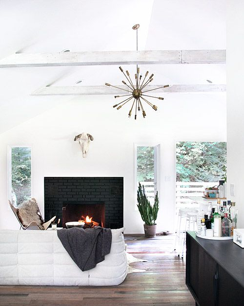 A black brick fireplace contrasts beautifully against this white washed Catskills home.