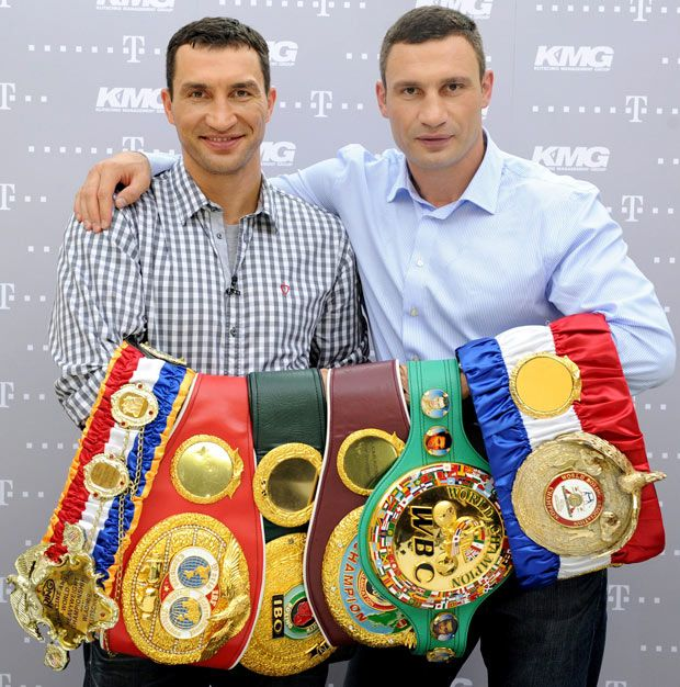 Ukranian heavyweight boxers Wladimir (L) and Vitali Klitschko present their world championship belts after a video press conference in a hotel in Hamburg. Wladimir is WBA, WBO, IBO and IBF World Champion, while his older brother Vitali holds the WBC title. 6 July 2011.