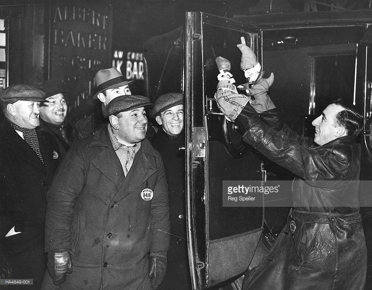 London taxi cab driver and member of the British Puppet Guild, Charles Tobbutt, entertains his fellow drivers between fares.1937