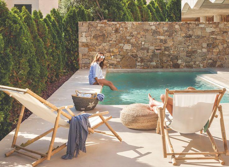 Mujer mojando los pies en la piscina con pared de piedra y tumbonas de madera y lona beige_331e81d