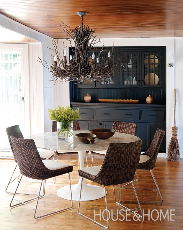 A branch chandelier hovers over a sleek tulip table in this modern-meets-country dining room, bringing a rustic vibe to the space. | Photographer: Stacey Brandford | Designer: Jennifer Worts