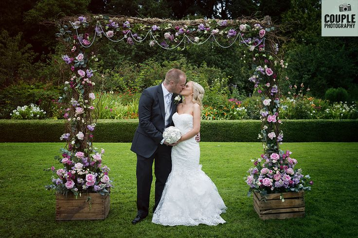 The newlyweds under the gorgeous flower arch. Weddings at Rathsallagh House…